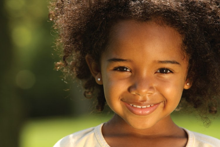Closeup of a dark-haired young girl with baby teeth smiling while outside
