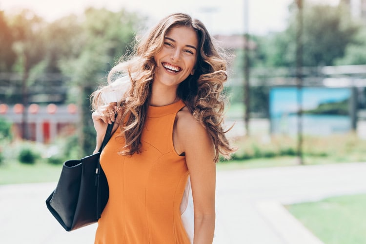 Brunette woman with large curls in an orange dress holds a black purse and smiles outside