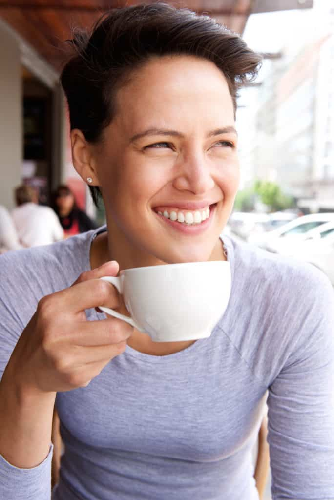 Smiling young woman drinking cup of coffee at cafe